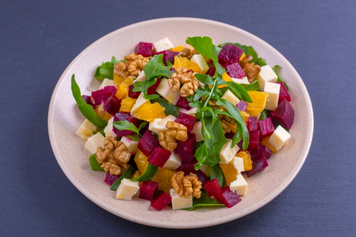 Healthy vegetarian salad with beetroot, green arugula, orange, feta cheese and walnuts on plate